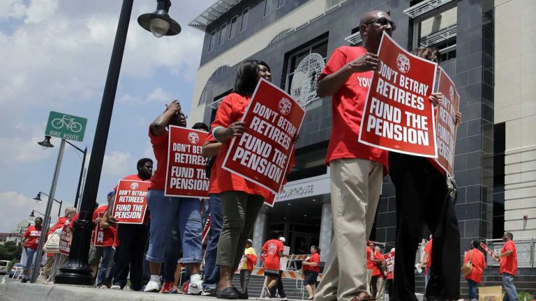 Union members carry protest signs as they march outside the Mercer County Criminal Courthouse before arguments June 25, 2014, over Gov Christie's plan to use pension payments to balance the budget. (AP Photo/Mel Evans)