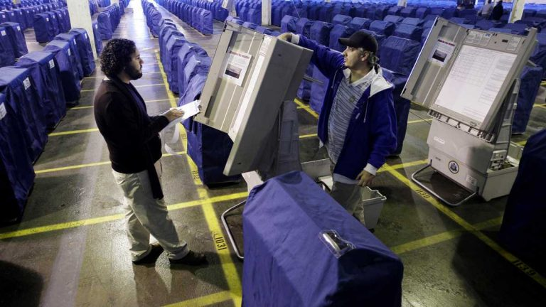 Workers inspect some of the voting machines Philadelphia uses. The city has budgeted $22 million to replace the machines. (AP file photo)