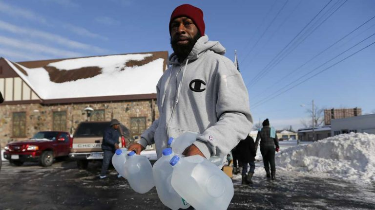Lemott Thomas carries free water being distributed at the Lincoln Park United Methodist Church in Flint, Michigan. (AP Photo/Paul Sancya)
