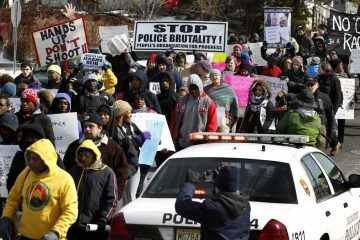 Demonstrators hold signs and shout as they march in protest of a fatal police shooting February 2015 in Bridgeton, NJ.(AP Photo/Mel Evans)