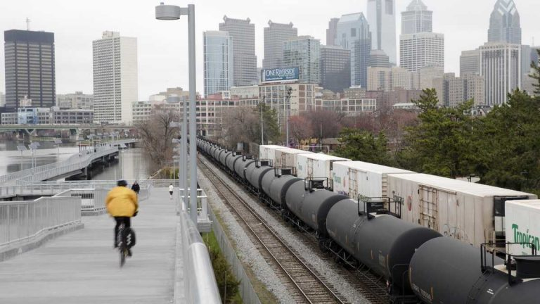 In April, a cyclist rides by train tank cars with placards indicating petroleum crude oil standing idle on the tracks in Philadelphia. Gov. Tom Wolf today released a study commissioned earlier this year to make recommendations on preventing oil train accidents in Pennsylvania. (AP Photo/Matt Rourke)