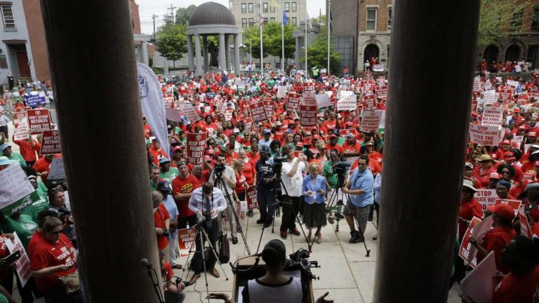 A large crowd of public employee union members fill the plaza and street in front of the Statehouse during a May protest in Trenton, New Jersey. They were protesting Gov. Chris Christie's pension-funding reductions. (AP file photo)