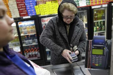 A woman pays for her groceries using state assistance at a supermarket (Seth Wenig/AP Photo)