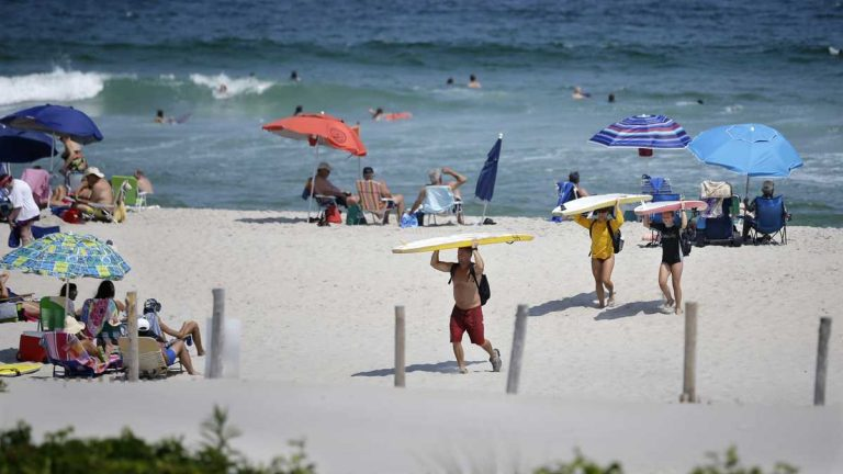 Surfers carry their surfboards across the beach as they call it a day