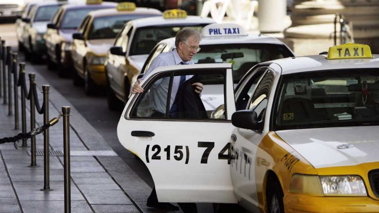 A man climbs into a cab at the 30th Street Station in Philadelphia. (Matt Rourke/AP Photo