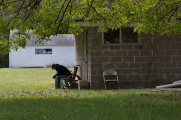 A resident sits outside of R & M guest home, a boarding home in Chesilhurst, New Jersey. (Lindsay Lazarski/WHYY)