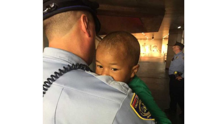 A SEPTA officer carries the child found wandering in LOVE Park Friday night. (Photo by Bill Newbold)