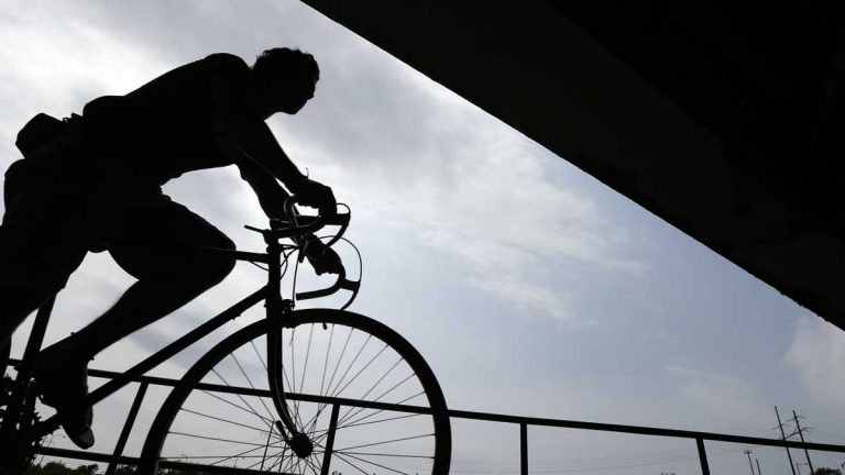 A cyclist rides beneath an overpass along the Schuylkill River in Philadelphia. (AP Photo/Matt Rourke