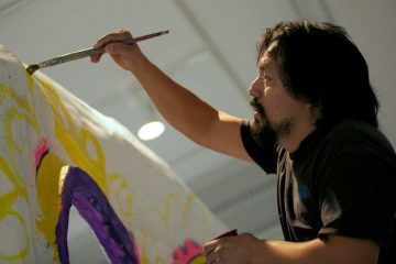 Philadelphia artist Cesar Viveros is shown painting a large skull for a Day of the Dead celebration at the Penn Museum. (Nathaniel Hamilton/for NewsWorks, file)