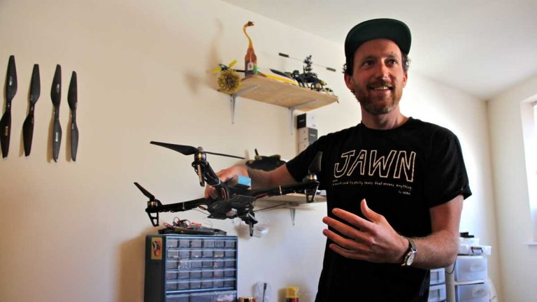 Maxwell Tubman of Steam Machine Pictures in South Philly holds one of his many copters. (Emma Lee/WHYY)