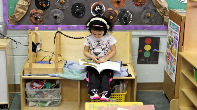 Kylee Mendez reads while she listens in her 4-year-old class at FELS Paley Center in North Philadelphia in this March, 2015, file photo. (Emma Lee/WHYY)