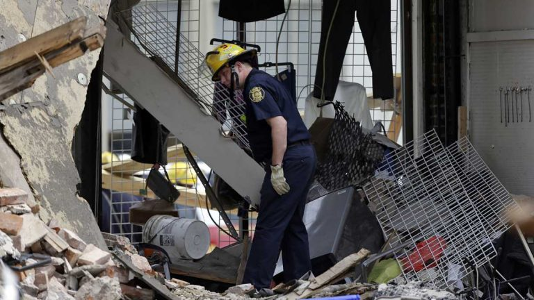 A firefighter walks through the aftermath of a building that collapsed in Center City