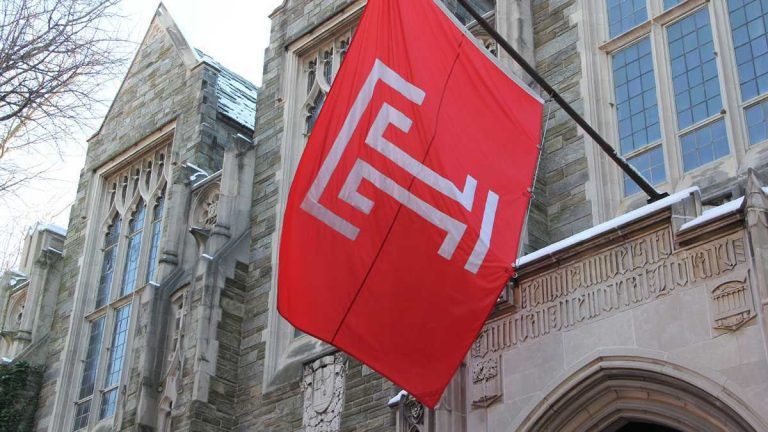 A Temple flag hangs above Sullivan Hall on the Temple University campus. (Emma Lee/WHYY)