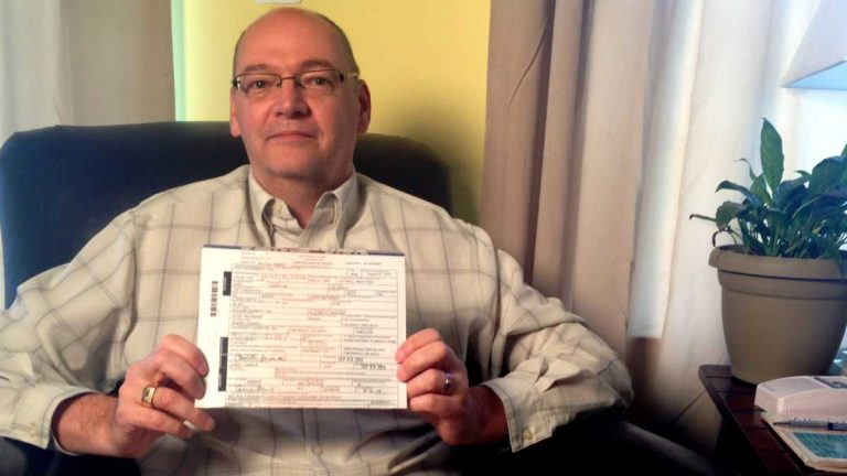 David Michener holds his husband's death certificate inside their Lewes home. The inclusion of Michener's name on the certificate is now part of a case before the U.S. Supreme Court. (Mark Eichmann/WHYY)