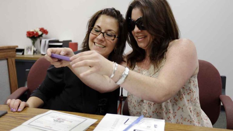 Tamara Davis, left, and Nicola Cucinotta snap a photograph of the marriage license they obtained at a Montgomery County office despite a state law banning such unions, Wednesday, July 24, 2013, in Norristown, Pa. Five same-sex couples have obtained marriage licenses in the suburban Philadelphia county that is defying a state ban on such unions.  (AP Photo/Matt Rourke)