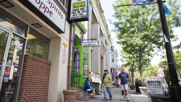 Peatones  se pasear en la calle  West Marshall en la parte Latina en Norristown, Pa. La colaboración entre la policia de Norristown y las autoridades federales de inmigración han provocado un número de deportaciones de residentes. (Lindsay Lazarski/WHYY)