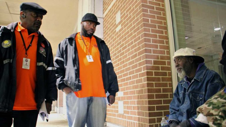 Homeless outreach workers talk with a man who has camped out on 12th Street in the shelter of the Pennsylvania Convention Center. (Emma Lee/WHYY)