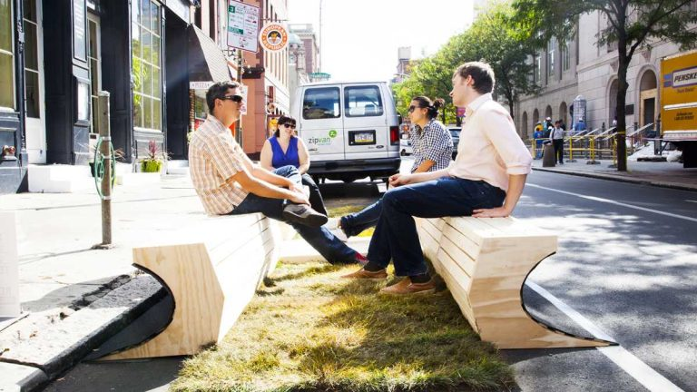 People sit at a 'parklet,' a parking spot converted into mini-park, on 3rd Street and Market Street in Philadelphia. (Brandon Reynolds/for NewsWorks)