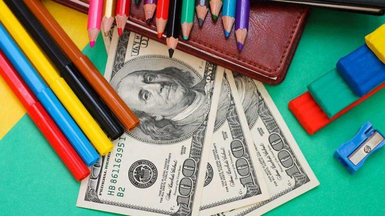 (School supplies, hundred dollar bills via ShutterStock)