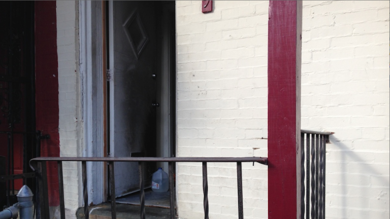 This Germantown front porch was where one of the firebombings took place over a five-week span in 2014 on East Coulter St. (Brian Hickey/WHYY)