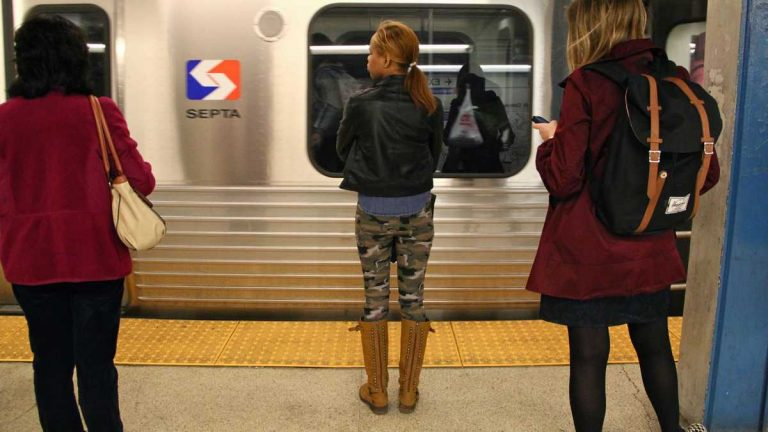 Commuters wait on a platform to board a SEPTA train. (NewsWorks file photo)