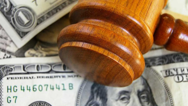 (<a href='http://www.shutterstock.com/pic-99045299/stock-photo-closeup-of-a-gavel-on-cash-from-above.html'>Image</a> courtesy of Shutterstock.com)