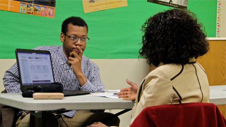 Will Bethea of Pennsylvania Health Access Network counsels a prospective enrollee during a sign-up session at the Coleman Library in Northwest Philadelphia. His group has helped nearly 400 people enroll in Medicaid since eligibility expanded in the state. (Emma Lee/WHYY)