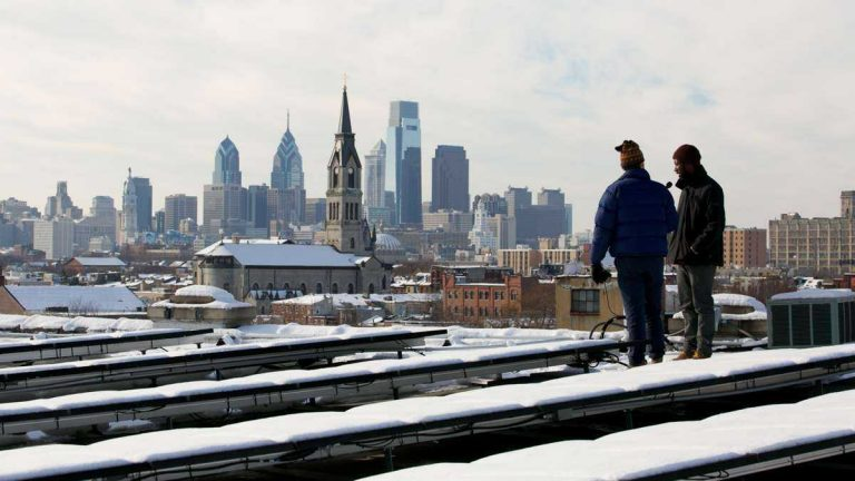 Snow-covered solar panels are shown on the rooftop of the Crane Arts building in Philadelphia's South Kensington neighborhood. (Nathaniel Hamilton/WHYY, file)
