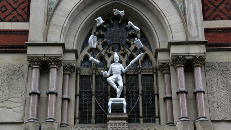 'Young Punch Juggling' by Connecticut-based artist Robert Taplin is the second in an ongoing series of temporary sculptures erected onto the façade of PAFA's historic building on North Broad Street. (Emma Lee/WHYY)