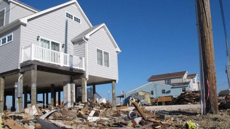 This file photo shows how the home on the left in Tuckerton, N.J., emerged from Superstorm Sandy intact, while the home to the right was severely damaged. FEMA has agreed to reopen more than 140,000 claims from people who say they were drastically underpaid by the federal flood insurance program for Sandy damage.  (Wayne Parry/AP Photo)