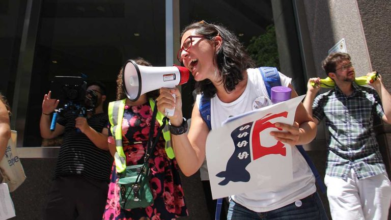 Xelba Gutierrez leads a protest  demanding that the Democratic National Convention reveal its sources of funding. (Emma Lee/WHYY)