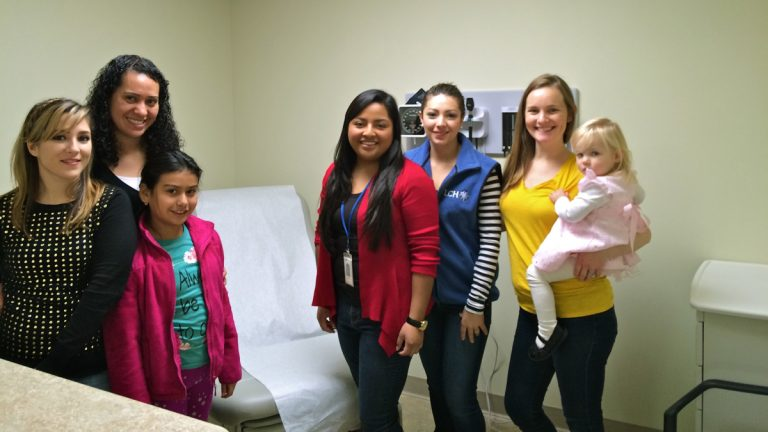 La Comunidad Hispana is opening a new health center in Oxford to serve growing numbers of Spanish speakers and low-income clients. Staff members (from left) member relations specialist Liliana Hernandez; front-to-end supervisor Cristina Gonzalez with her daughter, Shayla Nava; registered nurse Anel Medina; system application specialist/lead medical assistant Jeinny Garcia; and director of business operations and programs Amy Lambert with her daughter, Caroline, pose in one of the new exam rooms. (Photo courtesy of La Comunidad Hispana)