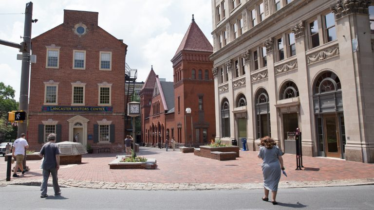Pedestrians walk toward the downtown visitors center and Central Market in Lancaster, Pennsylvania. (Lindsay Lazarski/WHYY)