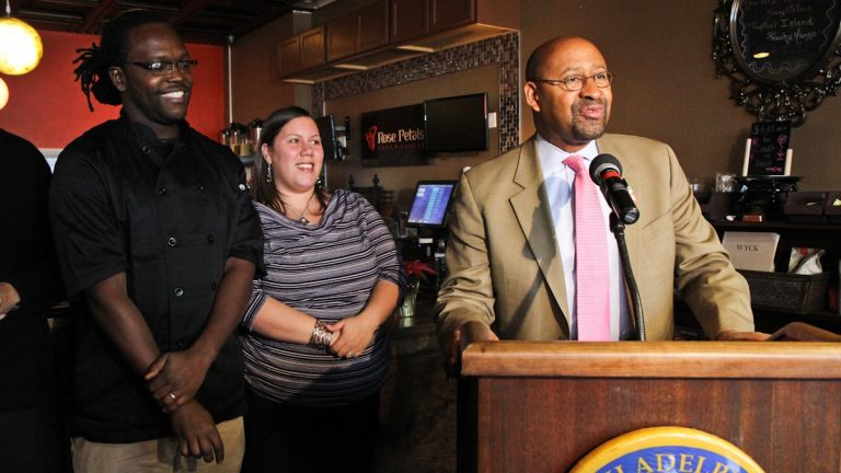 Desmin and Jania Daniels, owners of Rose Petals Cafe in Germantown, look on as Mayor Michael Nutter talks about the