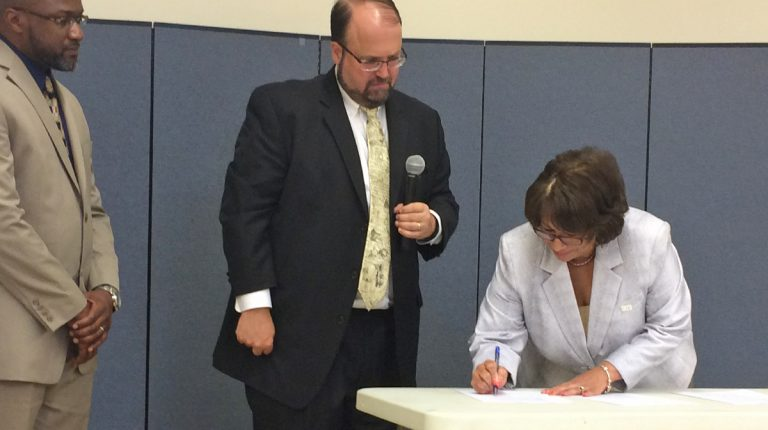 Harrisburg Mayor Eric Papenfuse (center) and Hamilton Health CEO Jeannine Peterson sign a memorandum of understanding for the new lead testing and abatement partnership. (Emily Previti/WITF)