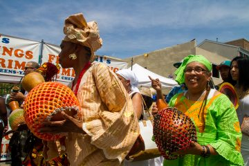 Women play the sekere, or shaker, a traditional instrument of the Yoruba people of Nigeria, as they make their way toward the South Street Bridge during a procession at the Odunde Festival. (Brad Larrison/for NewsWorks)