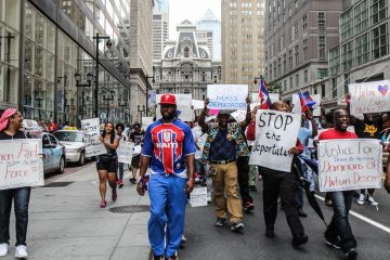 Members of the Philadelphian Haitian community march down Market Street Thursday afternoon chanting 'boycott the D.R.!' (Kimberly Paynter/WHYY)