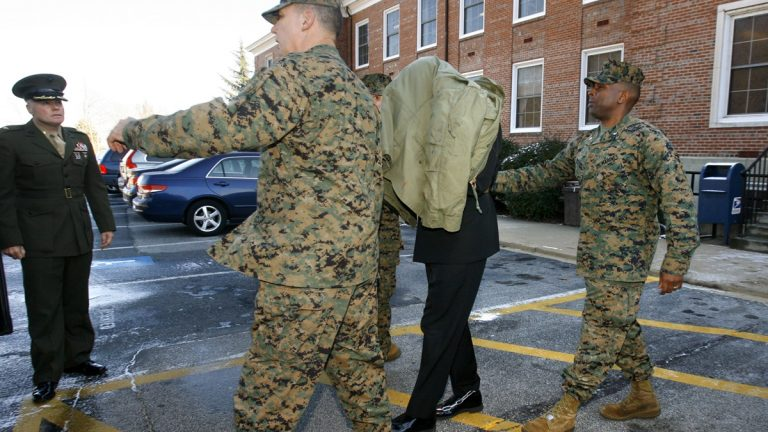 Lt. Cmdr. John Thomas Matthew Lee is seen under a jacket as he was escorted in shackles from his general court martial at Marine Corps Base Quantico Virginia in 2007. The HIV-positive Navy chaplain was then sentenced to two years in prison after pleading guilty to forcible sodomy and other charges. On Monday, Lee pleaded guilty in federal court in Delaware to production and distribution of child pornography. (AP Photo/Jacquelyn Martin)