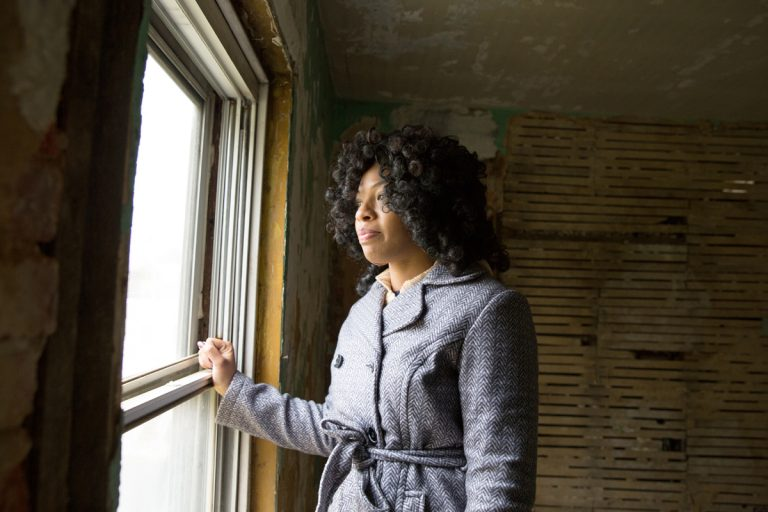 Nymiura Lee stands in the third floor bedroom of her grandparents home in North Philadelphia.  Conditions in the home became so bad the family had to move out.  (WHYY/Lindsay Lazarski)
