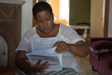 LaTonia Lee looks through her daughter's Individual Education Plan that was prepared in Georgia.  (Lindsay Lazarski/WHYY)