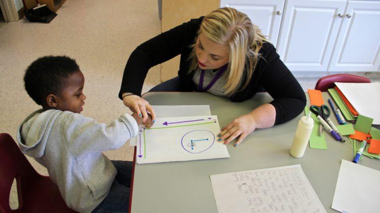 Pre-K teacher Danielle Slipp shows Quincy Hylaris how to make an L. (Emma Lee/WHYY)