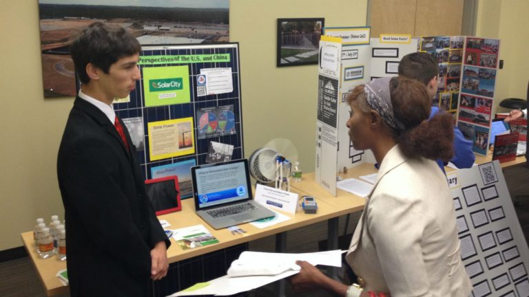 Sussex Tech student Trevor Roe (left) presents a project based on his time in China. (Avi Wolfman-Arent, NewsWorks/WHYY)