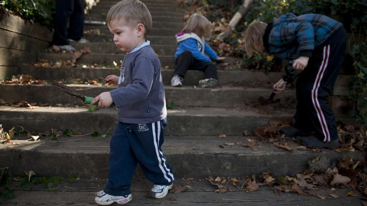 Isaiah Hoke, 2, of Germantown, helps clear dirt from the steps to Fernhill Park on Love Your Park Day. (Tracie Van Auken/for NewsWorks, file)