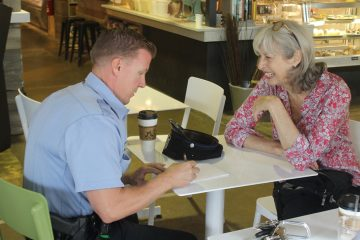Officer Robert Mahan speaks to Chestnut Hill resident Sue Hankin during a recent 'Coffee With A Cop' event. (Matt Grady/for NewsWorks)