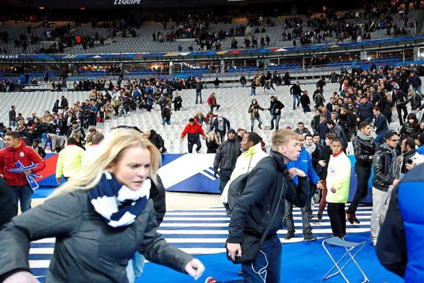 Spectators run from the Stade de France stadium Friday night after explosions were heard nearby. Several Millersville University students were in the crowd. (AP photo)