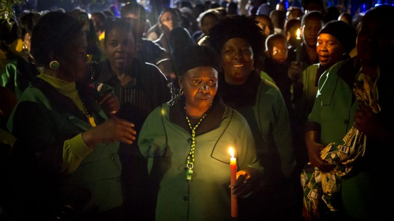 Members of the African National Congress Womens League hold candles and sings songs in memory of Nelson Mandela outside his old house in Soweto, Johannesburg, South Africa on Friday. (AP Photo/Ben Curtis)