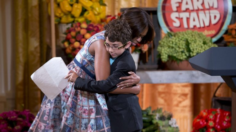 First lady Michelle Obama hugs Braeden Mannering, during the