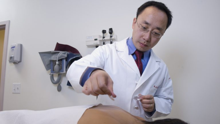 Dr. Jun Mao, a specialist in alternative therapies in oncology, prepares a patient for an acupuncture session. (Photo courtesy of University of Pennsylvania)