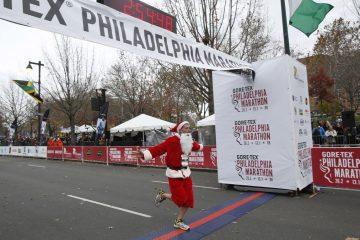 Brian Lang, or 'Santa,' finishes the GORE-TEX Philadelphia Marathon on the Benjamin Franklin Parkway on Nov. 22, 2015. (Stephanie Aaronson/for Newsworks)