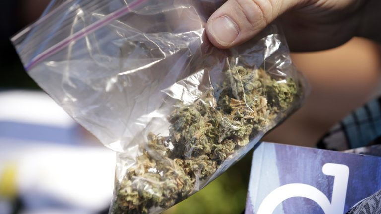 A man pulls out a bag of marijuana to fill a pipe. (AP Photo/Elaine Thompson, file)